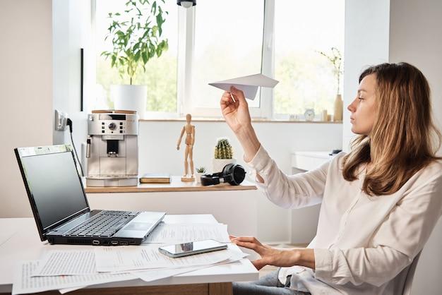 Женщина играет с бумажной простыней в домашнем офисе, откладывает удаленную работу