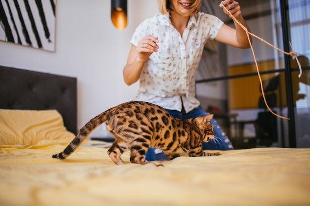 Woman plays with a rope with bengal cat