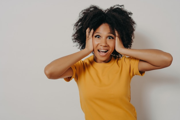 耳を腕で塞ぐ女性は、ハードロックや大音量の音楽を聴きたくない。大きな音や望まない会話を避けて手で頭を覆うノイズを無視するアフリカ系アメリカ人の若い女性