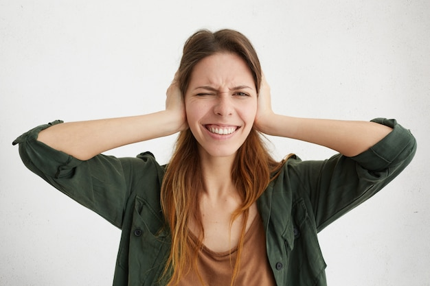 Woman plugging ears with fingers closing her eyes not wanting to listen noise