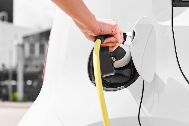 Женщина, включающая электромобиль на электрической зарядной станции на открытом воздухе со зданием. экологичная автомобильная концепция.