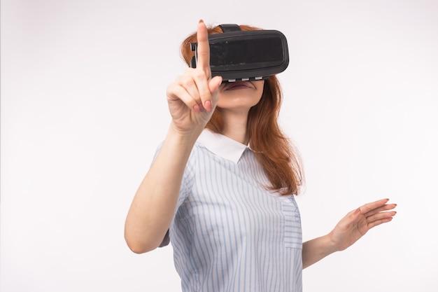 白い背景の上の仮想現実によってタッチスクリーンを押す女性のポイント。 vrヘッドセットメガネデバイス