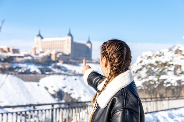Woman pointing at the alcazar of toledo. snow landscape.