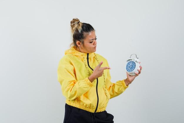 スポーツスーツの目覚まし時計を指して、物思いにふける、正面図を探している女性。