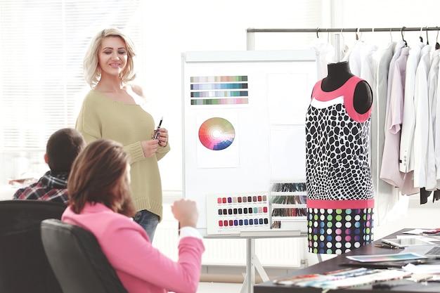 同僚とどの色を選ぶべきかを話し合っている間、見本のカラーパレットを指している女性。
