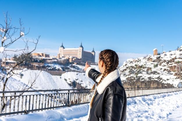 Женщина, указывающая на алькасар в толедо. снежный пейзаж.
