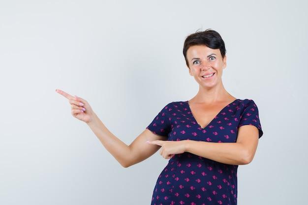 ドレスを着て左上隅を指差して陽気に見える女性。