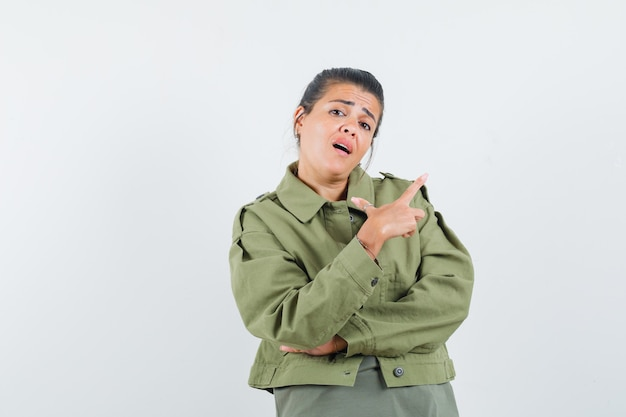 여자 재킷, t- 셔츠의 오른쪽 상단 모서리를 가리키고 자신감을 찾고.