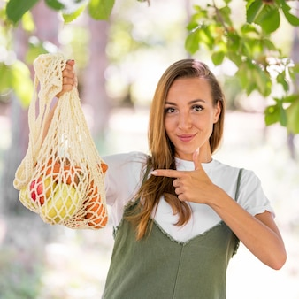 Woman pointing to a biodegradable bag with goodies
