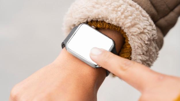 Donna che punta a uno smartwatch vuoto