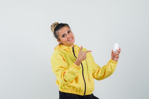 Donna che indica alla bottiglia di pillole in tuta sportiva e guardando fiducioso, vista frontale.