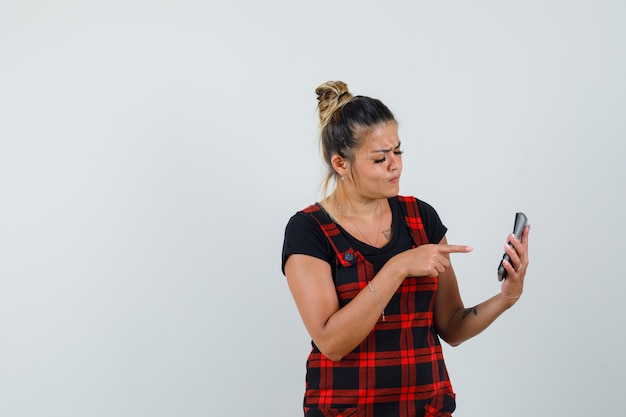 Woman pointing at calculator in pinafore dress and looking confused. front view.