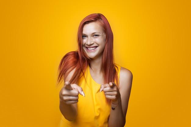 Женщина указывает прямо и улыбается в желтом платье на стене