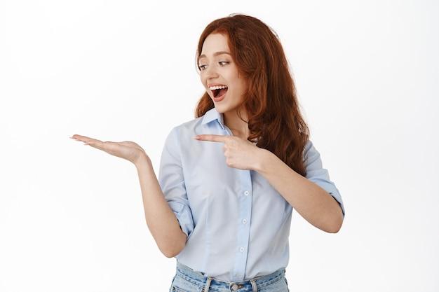 指を指して、開いた手で製品を見て、手のひらで素晴らしいブランドアイテムを示し、白のブラウスに立っている女性
