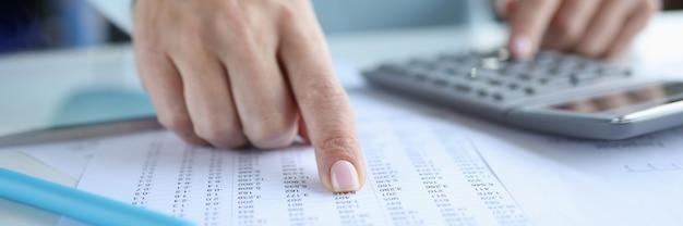 Женщина указывая пальцем на документ с числами и рассчитывая на крупный план калькулятора