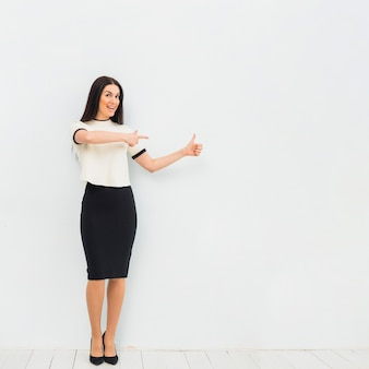 Woman pointing finger away and showing thumb up