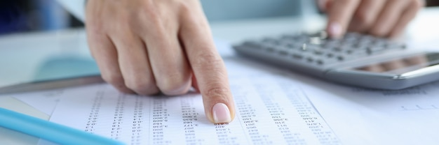 Woman pointing finger at document with numbers and counting on calculator closeup