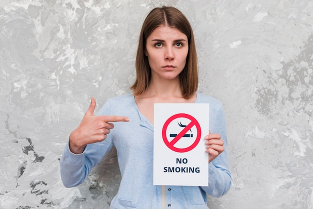 Woman pointing finger at no smoking poster standing near weathered wall