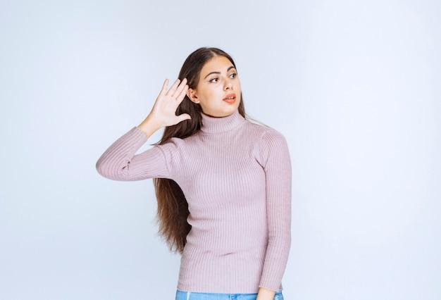 잘 들을 수 없기 때문에 귀를 가리키는 여자.