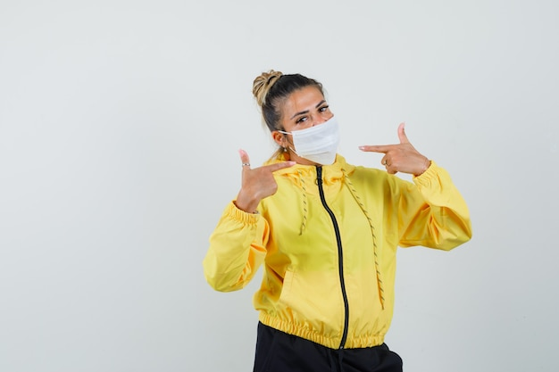Woman pointing at her mask in sport suit front view.