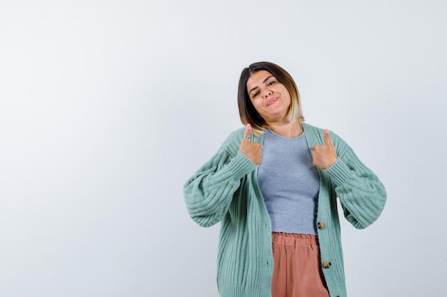 Donna che punta a se stessa in abiti casual e che sembra orgogliosa. vista frontale.