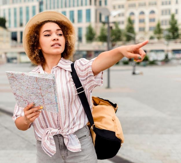 Женщина, указывая в направлении, держа карту