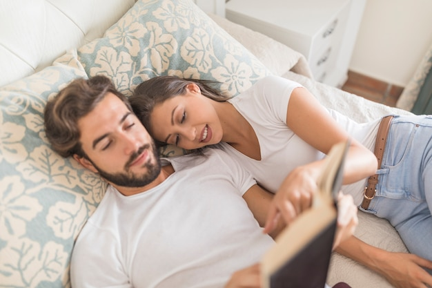 Woman pointing at interesting place in book for boyfriend