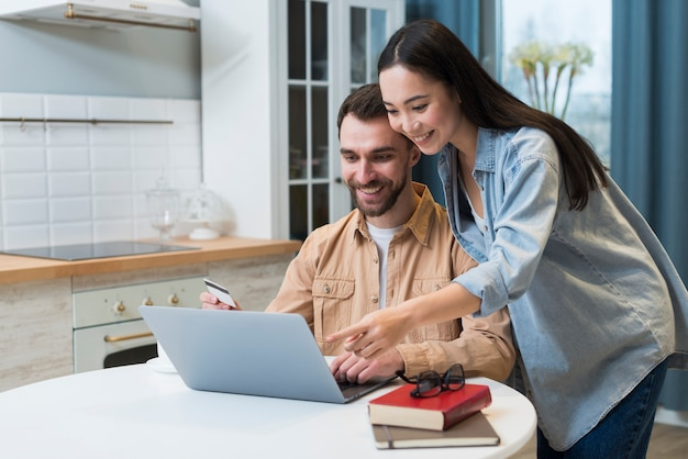 Woman pointing to laptop for man to buy online