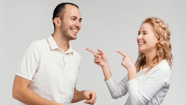 Woman pointing at man laughing