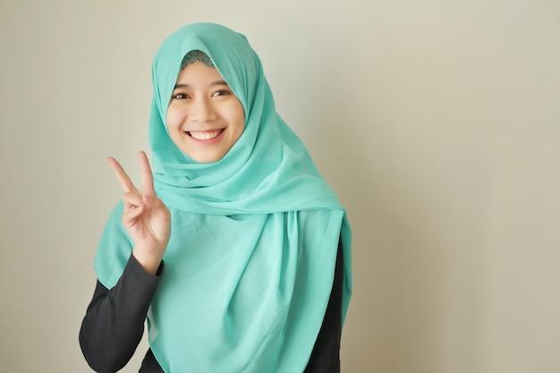 2番を指す女性、アジアのイスラム教徒の女性モデルの勝利の手のジェスチャー