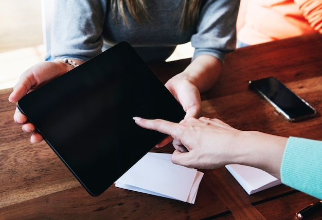 Женщина, указывающая на экране цифрового планшета