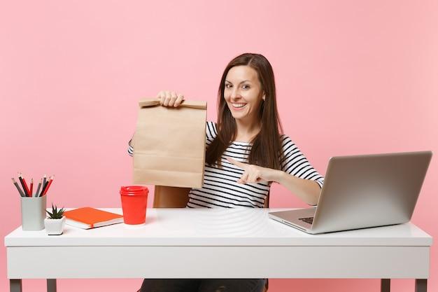 Женщина указывая на коричневый ясный пустой пустой бумажный мешок ремесла, работа в офисе с компьтер-книжкой изолированной на розовой предпосылке. доставка продуктов курьерской службой из магазина или ресторана в офис. скопируйте пространство.