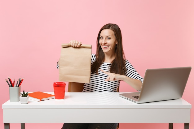 Женщина, указывая на коричневый чистый пустой пустой бумажный пакет ремесла, работа в офисе с ноутбуком