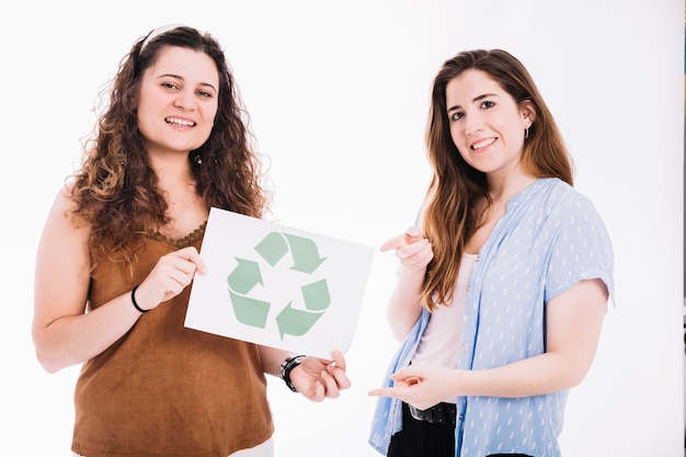 Woman pointing to recycle placard hold by her friend against white backdrop