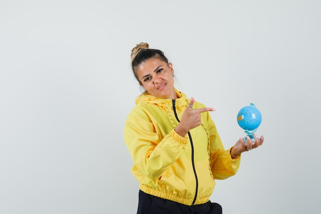 Woman pointing at school globe in sport suit and looking positive , front view.
