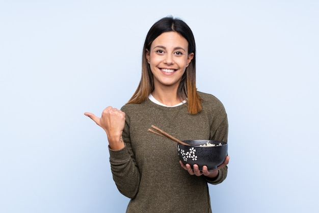 Woman pointing to the side to present a product while holding a bowl of noodles with chopsticks