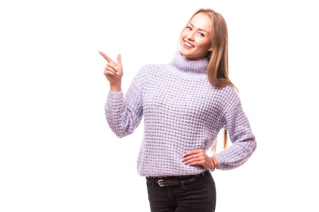 Donna che punta al lato in piedi in tutta la lunghezza - isolato sul muro bianco.