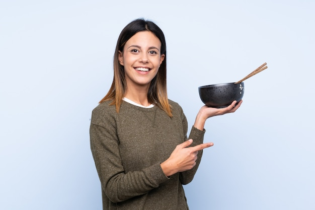 Woman pointing to the side while holding a bowl of noodles with chopsticks