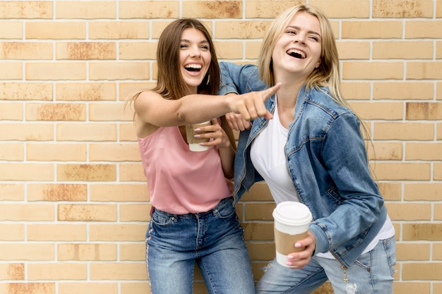 Woman pointing something to her friend