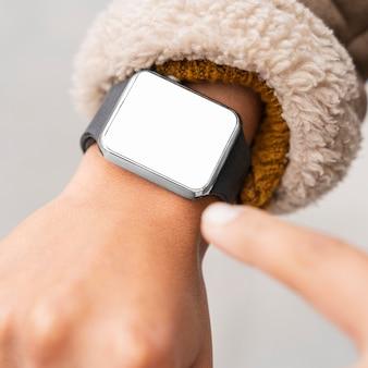 Женщина, указывая на пустой смарт-часы крупным планом