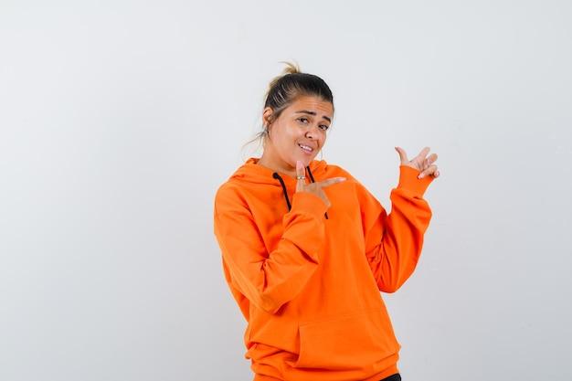Женщина в оранжевой толстовке с капюшоном указывает на правую сторону и выглядит уверенно