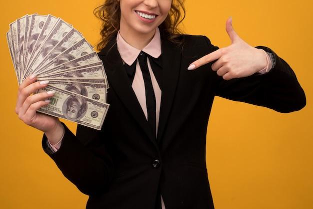 黄色の背景に隔離された彼女の指でお金のスタックを指している女性。