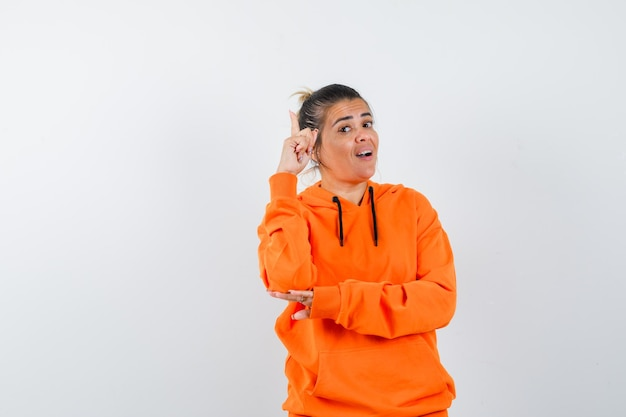 Woman pointing up, finding excellent idea in orange hoodie and looking happy
