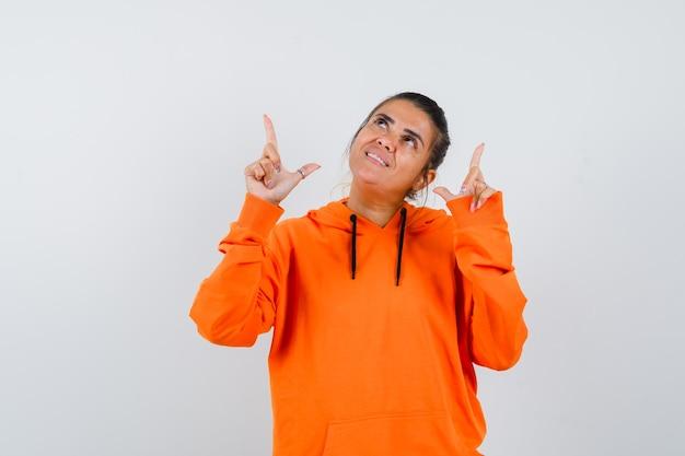 Donna che indica in su in felpa con cappuccio arancione e sembra speranzosa