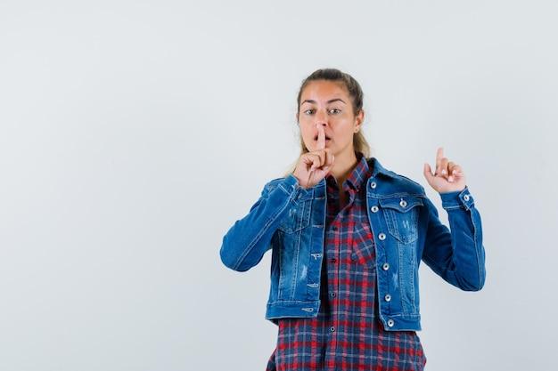 Женщина указывая вверх, показывая жест молчания в рубашке, куртке и глядя осторожно. передний план.
