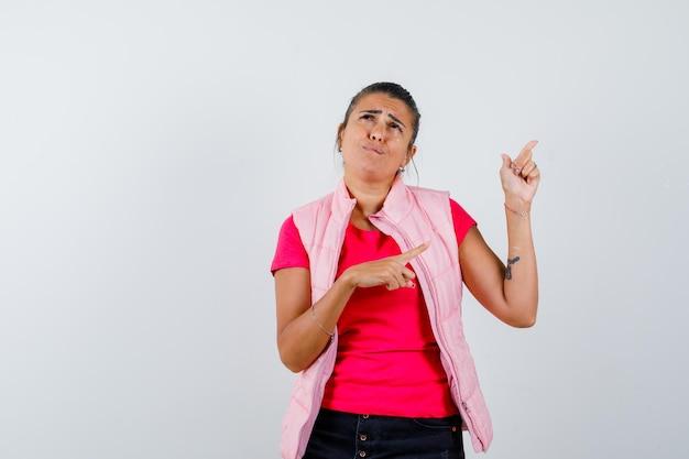 Donna che indica in t-shirt, gilet e sembra triste