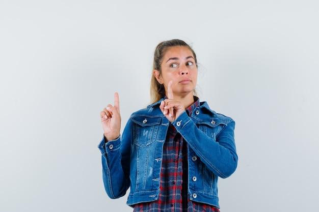Женщина указывая вверх, глядя в сторону в рубашке, вид спереди пиджак.