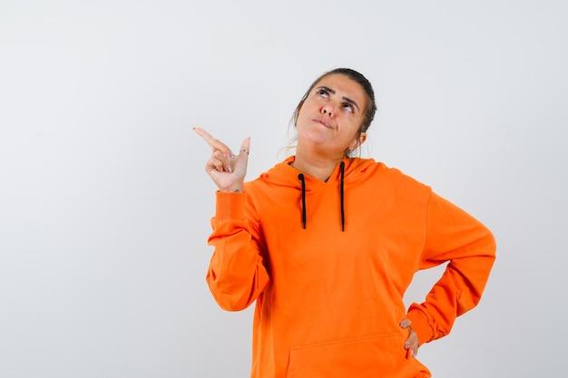 Donna che indica l'angolo in alto a sinistra in felpa con cappuccio arancione e sembra pensierosa