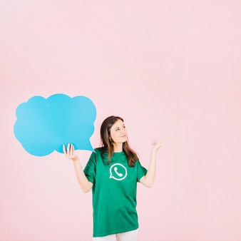 Woman pointing upwards holding empty blue speech bubble