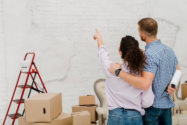 Woman pointing at wall for man